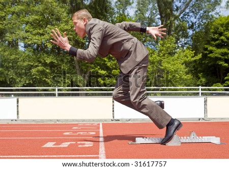 Young businessman explosively surging out of the starting blocks of his career - stock photo