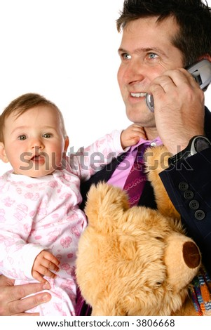 Young businessman father holding his baby, with teddy bear clutched under one arm as he makes a phone call. Concept of family life and work pressure. - stock photo