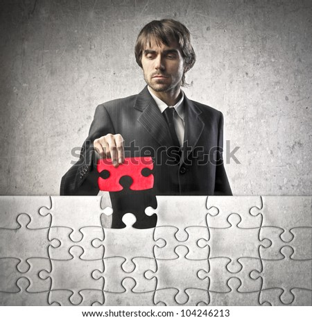 Young businessman finishing a puzzle - stock photo