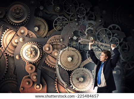 Young businessman fixing gears mechanism with wrench - stock photo