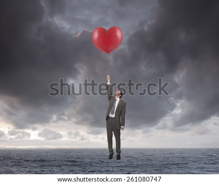 young businessman flying over the sea with heart shaped balloons - stock photo