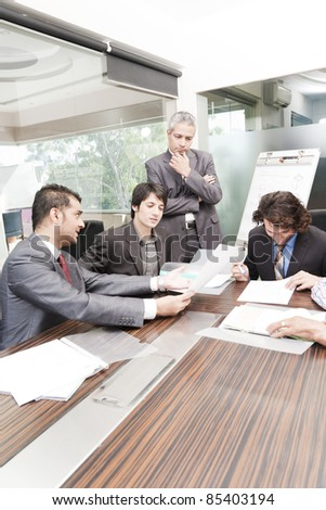 young businessman giving presentation to a group of multi racial group of colleagues, a group of diversed businessmen. - stock photo