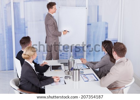 Young businessman giving presentation to colleagues at office - stock photo