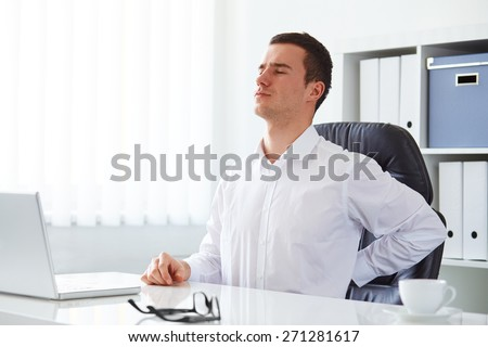 Young businessman has backache at work with a laptop - stock photo