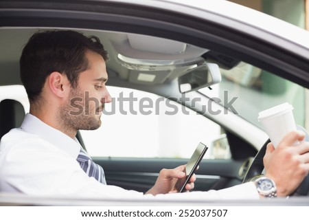 Young businessman having a coffee in his car - stock photo