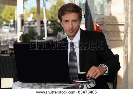 Young businessman having coffee outdoors - stock photo