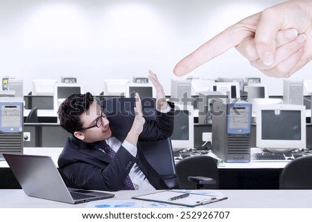 Young businessman having problem in the office and bullied by someone - stock photo