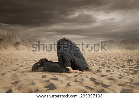 Young businessman hiding head in the sand - stock photo