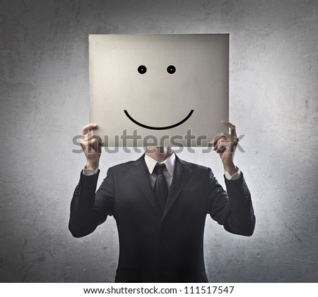 Young businessman hiding his face with a white billboard with a smiley face on it - stock photo