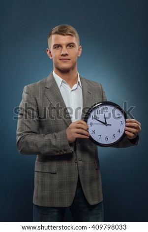 young businessman holding a clock  - stock photo