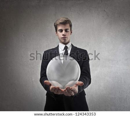 Young businessman holding a glass bubble - stock photo