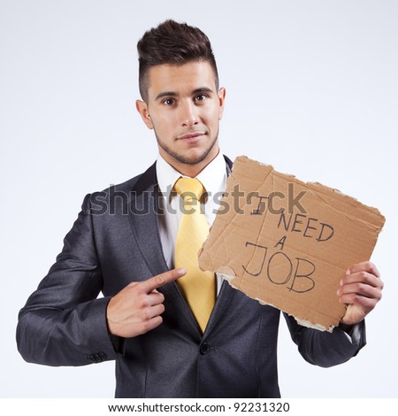 Young businessman holding a piece of cardboard saying he needs a job - stock photo