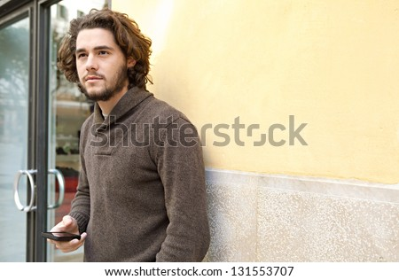 Young businessman holding a smart phone while standing by the entrance of an office building, outdoors. - stock photo