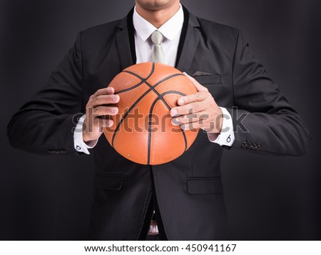 Young businessman holding basketball ball isolated on black background - stock photo