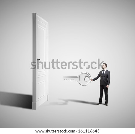 young businessman holding big key with closed door - stock photo