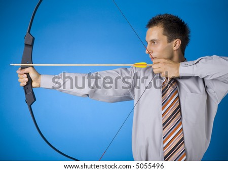 Young businessman holding bow and shooting to target. Blue background - stock photo