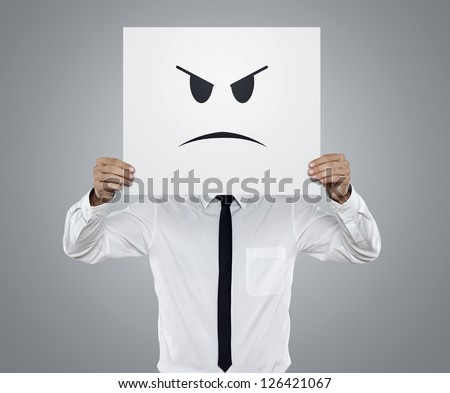 Young businessman holding card with a angry face on it isolated on gray background - stock photo