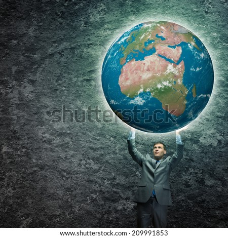 Young businessman holding Earth planet high above head. Elements of this image are furnished by NASA - stock photo
