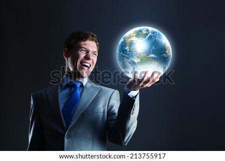 Young businessman holding Earth planet in hand. Elements of this image are furnished by NASA - stock photo