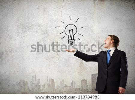 Young businessman holding electric bulb in palm - stock photo