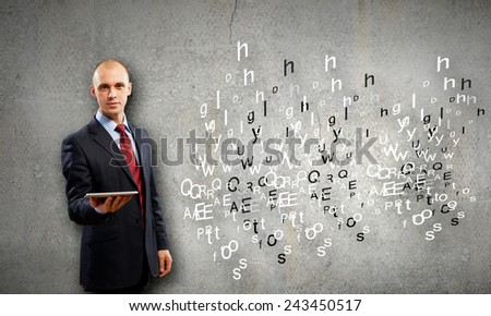 Young businessman holding in hand tablet pc - stock photo