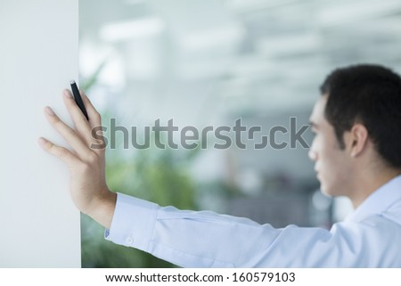 Young businessman holding pen and leaning on doorway in office - stock photo