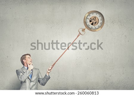 Young businessman holding pocket watch on rope - stock photo