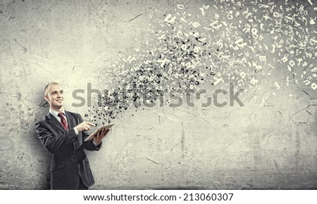 Young businessman holding tablet pc and letter flying in air - stock photo