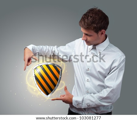 Young businessman holding virtual shield sign - stock photo