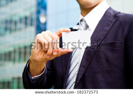 young businessman holding visit card in hand and standing in the front of office building  - stock photo