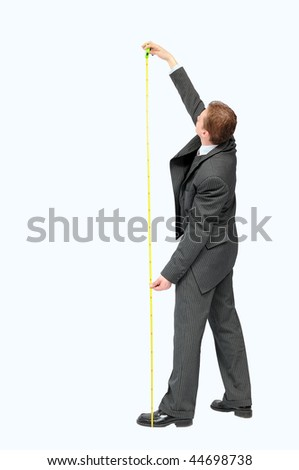 Young businessman holding yellow measuring tape and looking above. - stock photo