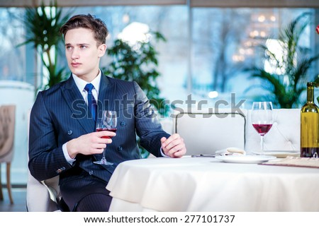 Young businessman in a bar. Confident businessman in formal wear sitting at a table in a restaurant while holding a glass of wine and looking ahead - stock photo