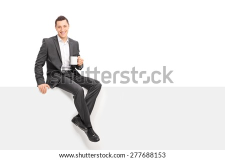 Young businessman in a gray suit holding a cup of coffee and sitting on a blank panel isolated on white background - stock photo