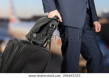 young businessman  in  a modern  stylish suit with  luggage in  the airport  - stock photo