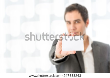 Young businessman in a suit holding up a blank white business card with copyspace for your contact details, identity or branding, with further lateral copyspace on an abstract background. - stock photo