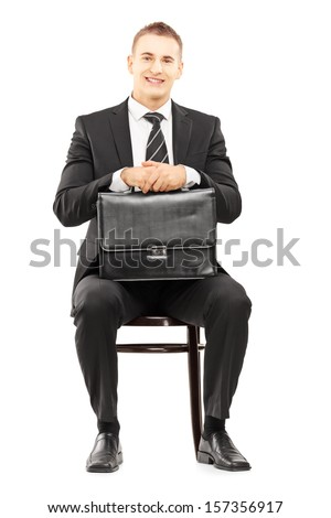 Young businessman in black suit holding a leather briefcase and waiting on a wooden chair isolated on white background - stock photo