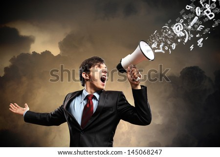 young businessman in black suit screaming into megaphone - stock photo