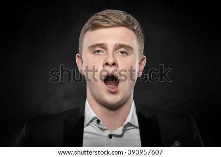 Young businessman in black suit yawning or enjoying. - stock photo