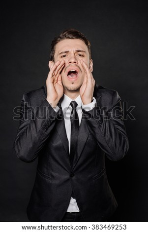 young businessman in black suit yelling with open hands. emotions, facial expressions, feelings, body language, signs. image on a black studio background. - stock photo