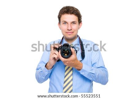 young businessman in blue shirt and necktie holds dslr camera, studio shoot isolated on white background - stock photo