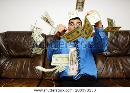 Young businessman in blue shirt sitting on the couch is surprised by the rain of money - stock photo