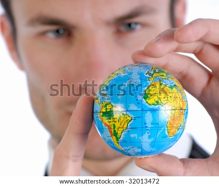 young businessman in  business suit holds model of globe in  hand and reflects - stock photo