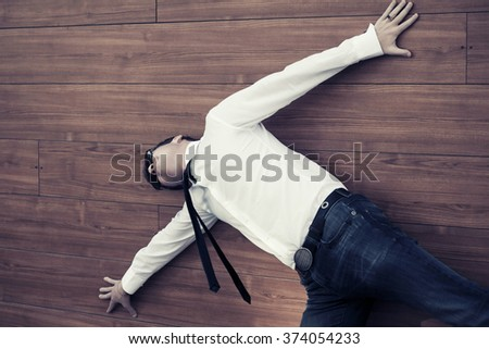 Young businessman in despair lying on the floor - stock photo