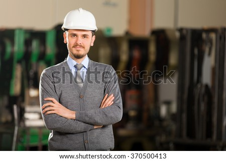 Young businessman in factory. - stock photo