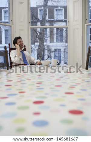 Young businessman in formals using cellphone at dining table - stock photo