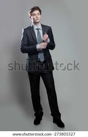 Young businessman in gray suit thinking or dreaming, on gray background - stock photo