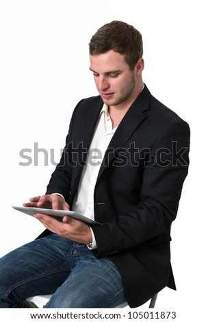 Young Businessman in jeans working on a tablet pc - stock photo