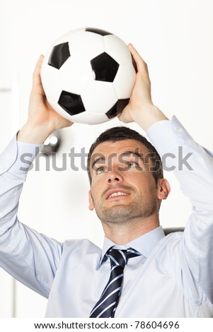 young businessman in office with ball in the hands - stock photo