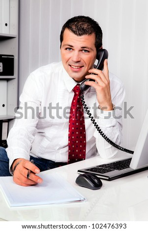 young businessman in office with telephone - stock photo