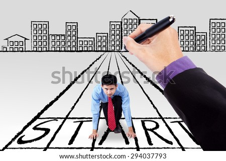 Young businessman in ready position on the start line and ready to start the competition with a guide of hand - stock photo